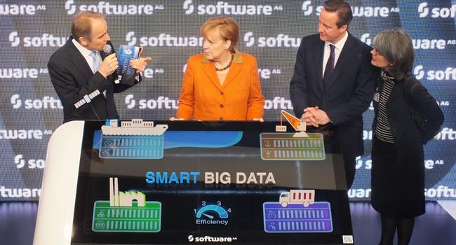 """קארל היינץ שטרייביך, מנכ""""ל SAG,  מסביר על יתרונות הארגון הדיגיטלי בעולם של Big Data. קנצלרית גרמניה אנגלה מרקל וראש ממשלת בריטניה דייויד קמרון, שעל אוזנו לוחשת המתרגמת מגרמנית לאנגלית, מאזינים"""
