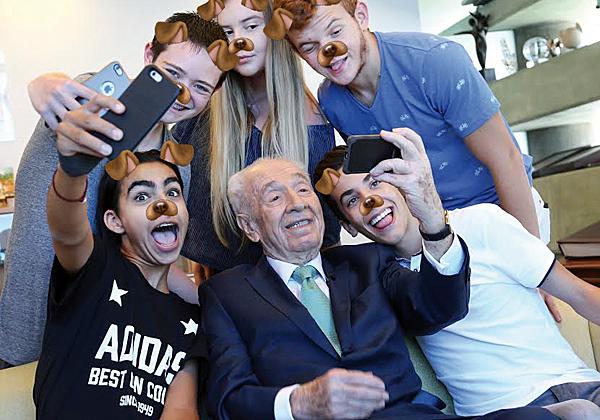 """הנשיא לשעבר, שמעון פרס ז""""ל, עם בני הנוער שמקושטים במסנני סנאפצ'ט. צילום: ידיעות אחרונות"""