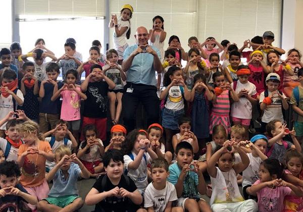 """אורי תדמור, מנהל חטיבת התפעול של KLA-Tecnor, והילדים עושים לבבות בקייטנה של החברה. צילום: יח""""צ"""