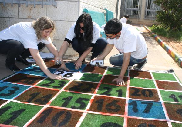 """עובדי טלדור מציירים משחקי רצפה ביום המעשים הטובים בבית הספר סיני, רמלה. צילום: יח""""צ"""