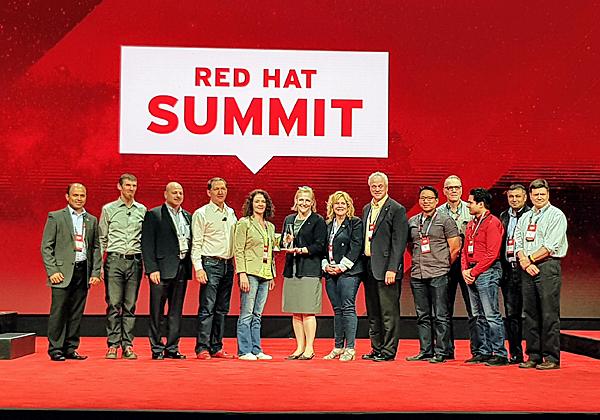 """כריס רייט, מנהל הטכנולוגיות הראשי של רד-האט, העלה לבמה את נציגי הלקוחות שזכו באות הוקרה השנה. בתמונה: רייט (שני משמאל) ג'ים וייטהרסט, מנכ""""ל רד-האט, ונציגי ענקית השילוח הבינלאומית UPS, אחת הזוכות. צילום: פלי הנמר"""
