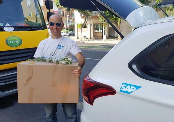 אסף אורטנר, מנהל פרויקטים בסאפ ישראל בדרך עם חבילת המזון ופרחים לחג. צילום: יח
