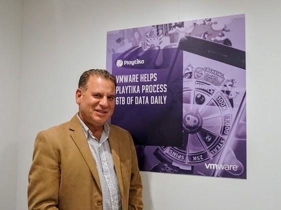 שמוליק ענתבי, מנהל בכיר ב-VMware מזרח אירופה בנוסף ליוון, קפריסין, מלטה וישראל. ליד השלט של פלייטיקה הישראלית, הלקוח המצטיין גלובלית בכנס VMworld 2018. צילום: פלי הנמר