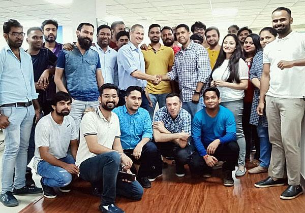 """אמיר זלצר (לוחץ יד) והצוות של מרכז הפיתוח של TeamScale בהודו. צילום: יח""""צ"""