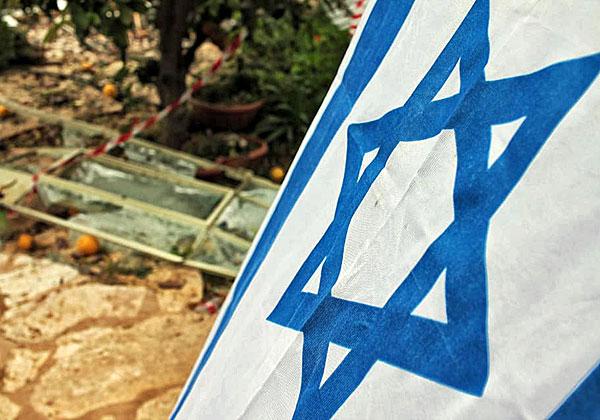 דגל ישראל על רקע הבית ההרוס של משפחת וולף במושב משמרת שבשרון. צילום: גילי חנוך