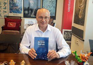 """תת ניצב בדימוס עו""""ד ד""""ר אורי אנגלהרד אוחז בספר החדש שכתב - סודות הניהול על פי פרשות השבוע. צילום: פלי הנמר"""