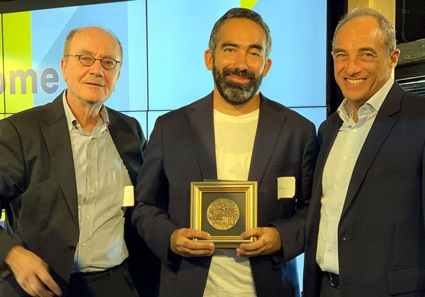 """רומן לוי, מנכ""""ל אורבן פלייס (במרכז), מקבל את הפרס מד""""ר דניאל רואש ומאדוארד קוקרמן. צילום: יח""""צ"""