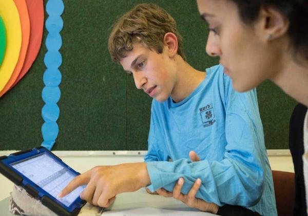 """עידן, תלמיד בחינוך המיוחד, וה-iPad. צילום: יח""""צ"""