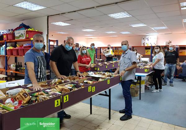 אורזים סלי מזון לקראת החג. עובדי שניידר אלקטריק ישראל. צילום: ג'רלדין רוסנטל