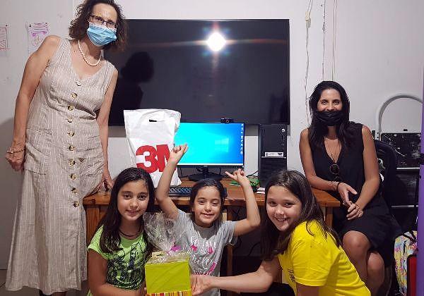 """מימין לשמאל: עינת שוכר מארגון מתן-United Way, בנות המשפחה שקיבלה מחשב מלוד, ואיזבל צדיקוב, מנהלת שלוחת 3M בישראל. צילום: יח""""צ"""