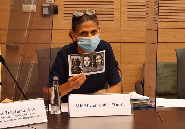 """ח""""כ מיכל קוטלר-וונש (כחול לבן) עם תמונות הגולשות שהתחפשו לקורבנות שואה. צילום: דוברות הכנסת"""
