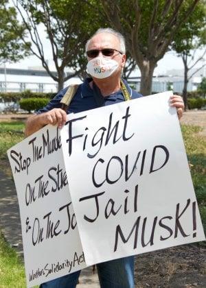הייחס לקורונה מקומם. מפגין נגד מאסק ומדיניות הגנת העבודים הרופפת מפני קורונה, בשערי מפעל טסלה. צילום: BigStock