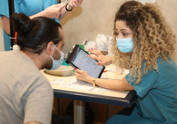 """אחות מסבירה לאחד המתחסנים על תהליך החיסון באמצעות האפליקציה. צילום: דוברות בית החולים רמב""""ם"""