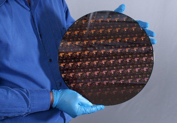 """חוקר של יבמ מציג וואפר המכיל המוני שבבי 2 ננו-מטר. צילום: יח""""צ"""